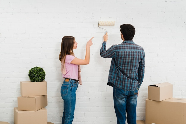 Junge frau, die seinen ehemann malt die wand mit lackrolle führt