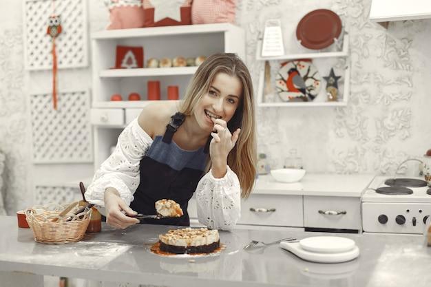 Junge frau, die selbst gemachten kuchen in der küche hält