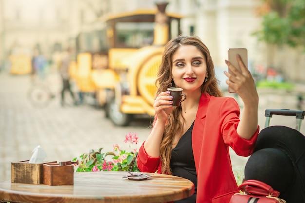 Junge frau, die selfie am café draußen nimmt