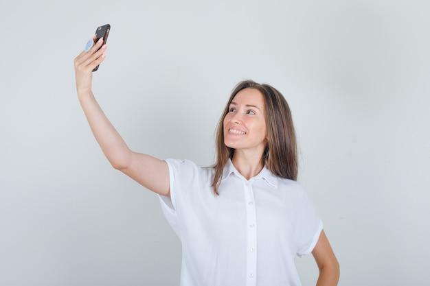 Junge frau, die selfie am telefon im t-shirt nimmt und fröhlich schaut