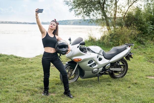 Junge frau, die selfie auf motorrad im freien macht