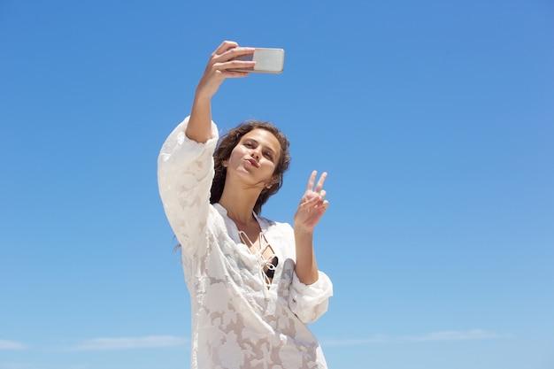 Junge frau, die selfie mit friedenshandzeichen nimmt