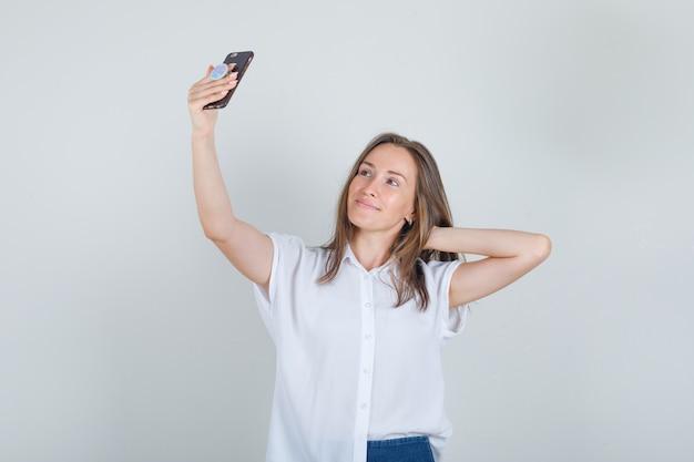 Junge frau, die selfie mit hand hinter kopf in t-shirt, jeans nimmt und fröhlich schaut