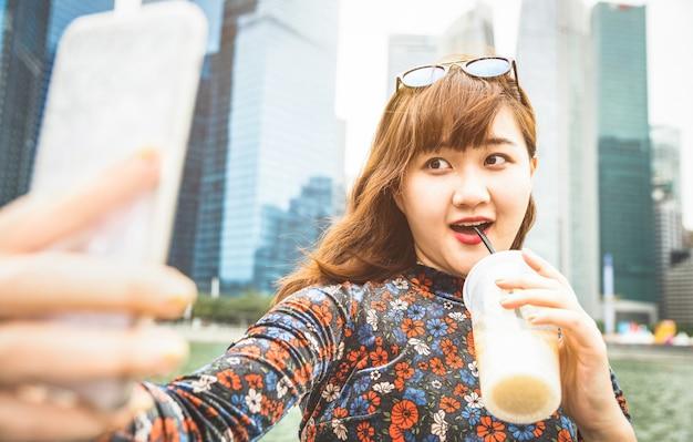 Junge frau, die selfie mit kaffee in singapur nimmt