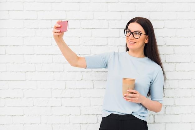 Junge frau, die selfie mit kaffeetasse nimmt