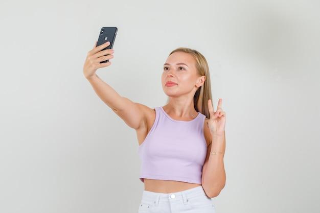 Junge frau, die selfie nimmt, indem sie v-zeichen im singulett zeigt