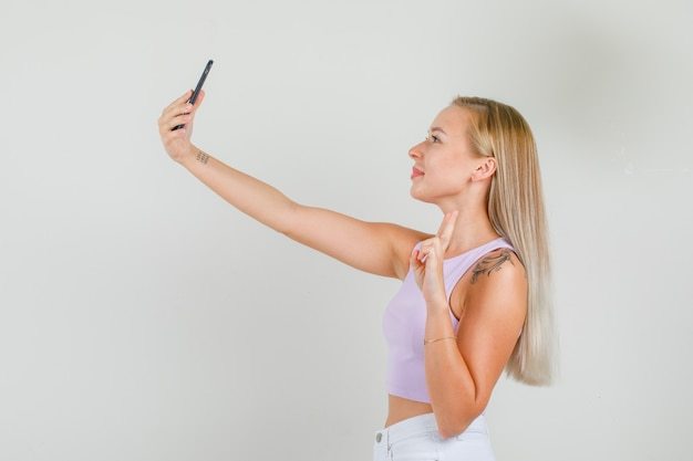Junge frau, die selfie nimmt, indem sie v-zeichen im unterhemd, minirock zeigt.