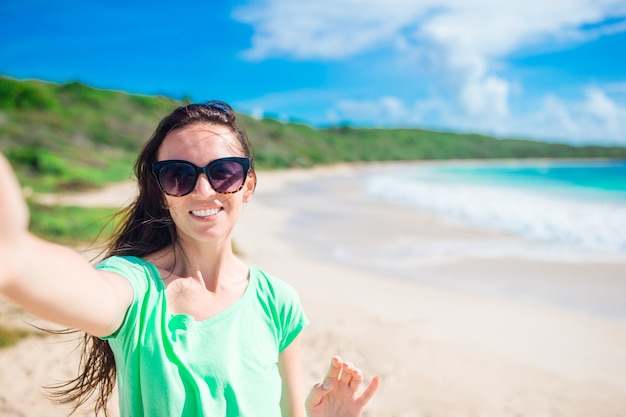 Junge frau, die selfie porträt auf dem strand nimmt