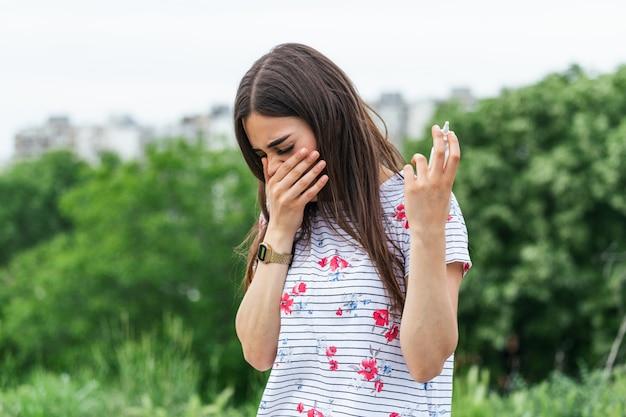 Junge frau, die servietten und spray für ihre allergie oder fieber, kalte und laufende nase im blühenden garten hält