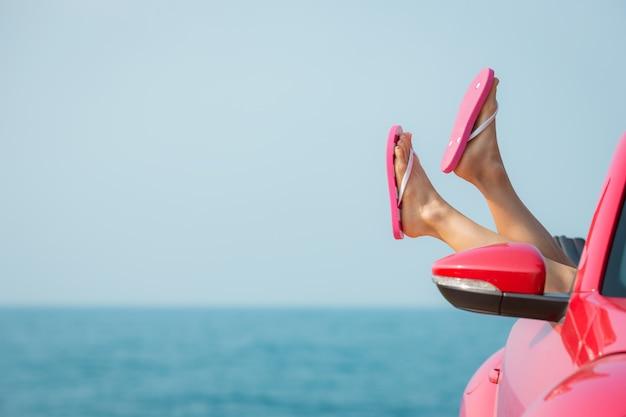 Junge frau, die sich am strand entspannt mädchen, das spaß im roten cabriolet gegen blauen himmel hat sommerurlaub und reisekonzept