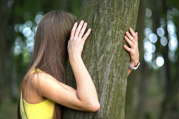 Junge frau, die sich an baumstamm lehnt und ihn mit ihren händen im sommerwald umarmt.