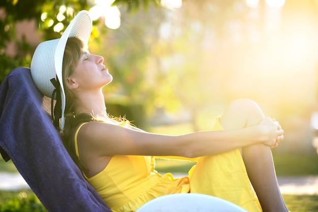 Junge frau, die sich an einem sonnigen sommertag im freien entspannt. glückliche dame, die sich auf einem bequemen strandkorb hinlegt