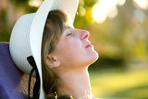 Junge frau, die sich an einem sonnigen sommertag im freien entspannt. glückliche dame im strohhut, der das denken träumt. ruhiges schönes lächelndes mädchen, das frische luft genießt, entspannen sie sich mit geschlossenen augen.