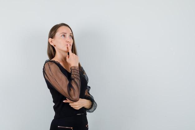 Junge frau, die sich auf etwas in der schwarzen bluse konzentriert und nachdenklich aussieht. vorderansicht. platz für text