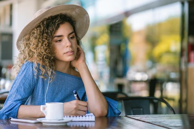 Junge frau, die sich entspannt und auf ein notizbuch schreibt, während sie eine tasse kaffee in einem café trinkt.