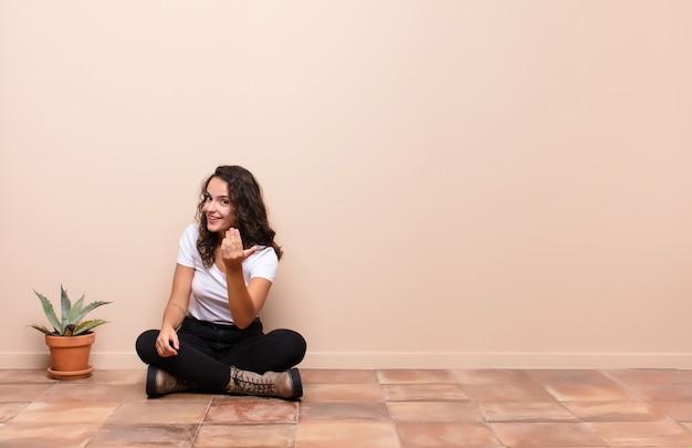 Junge frau, die sich glücklich, erfolgreich und selbstbewusst fühlt, sich einer herausforderung stellt und sagt, bringen sie es auf! oder sie auf einer terrasse begrüßen zu dürfen