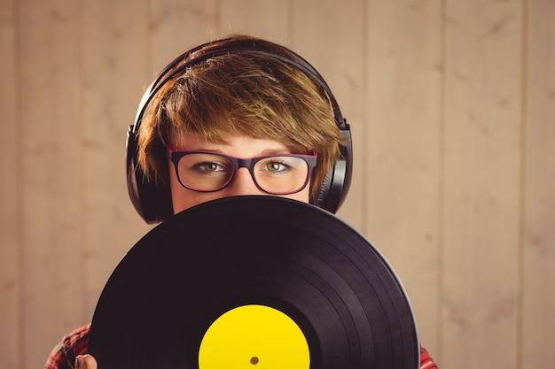 Junge frau, die sich hinter vinyl versteckt