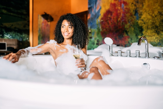 Junge frau, die sich im hydromassagebad entspannt, das in schaum bedeckt ist
