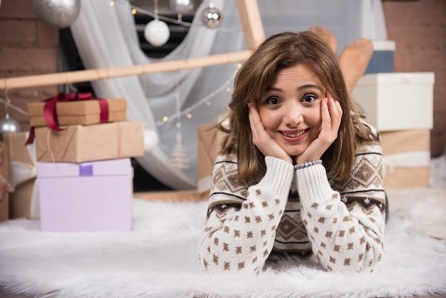 Junge frau, die sich im wohnzimmer im weihnachtlich dekorierten haus entspannt