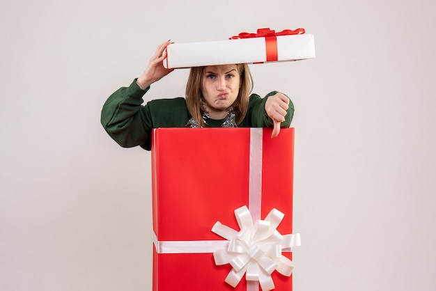 Junge frau, die sich in geschenkbox auf weiß versteckt