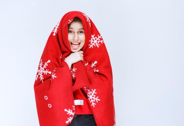 Junge frau, die sich mit einer roten warmen decke bedeckt.