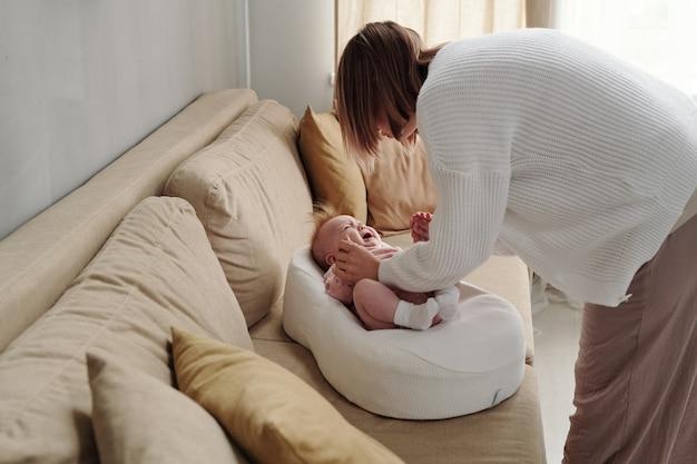 Junge frau, die sich mit ihrer süßen weinenden babytochter über die couch beugt
