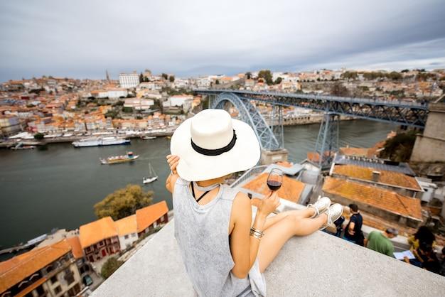 Junge frau, die sich mit porto-wein auf der terrasse mit schönem blick auf das stadtbild in porto, portugal, zurücklehnt