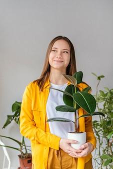 Junge frau, die sich um grüne pflanzen kümmert