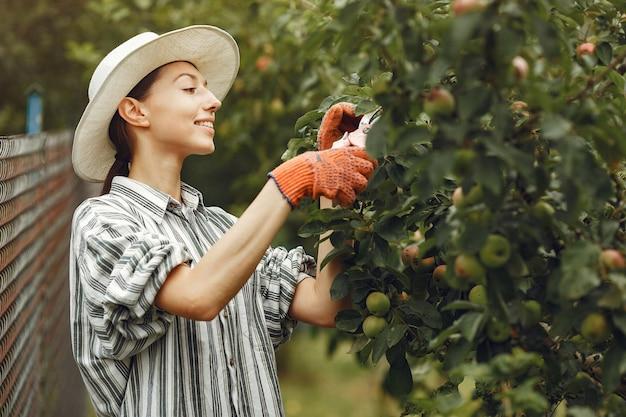 Junge frau, die sich um pflanzen kümmert. brünette mit hut und handschuhen. frau benutzen aveeuncator.