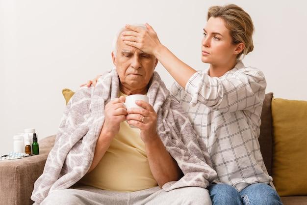 Junge frau, die sich zu hause um ihren älteren großvater mit erkältungssymptomen kümmert