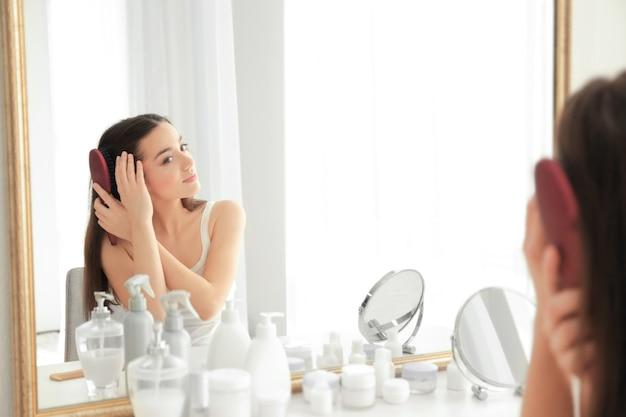 Junge frau, die sich zu hause vor dem spiegel die haare bürstet