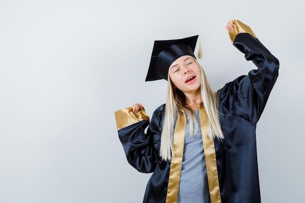 Junge frau, die siegergeste in absolventenuniform zeigt und glückselig aussieht.
