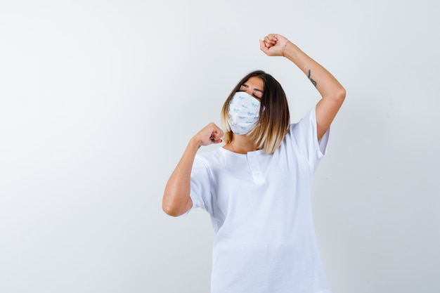 Junge frau, die siegergeste in t-shirt, maske zeigt und glück schaut. vorderansicht.