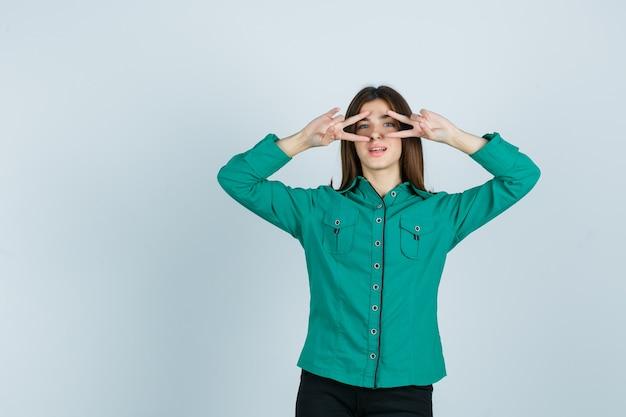 Junge frau, die siegeszeichen nahe augen in grünem hemd zeigt und selbstbewusst, vorderansicht schaut.