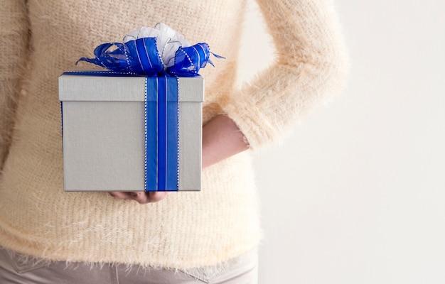 Junge frau, die silberne geschenkbox hinter ihr zurück versteckt