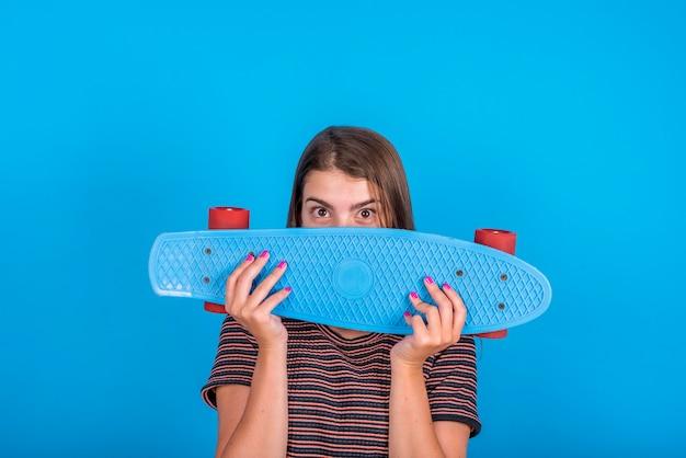Junge frau, die skateboard vor gesicht auf blauem hintergrund hält