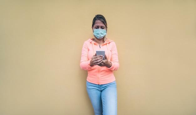 Junge frau, die smartphone-app im freien während covid-19 perion trägt sicherheitsmaske verwendet