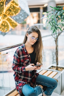 Junge frau, die smartphone auf bank im einkaufszentrum verwendet