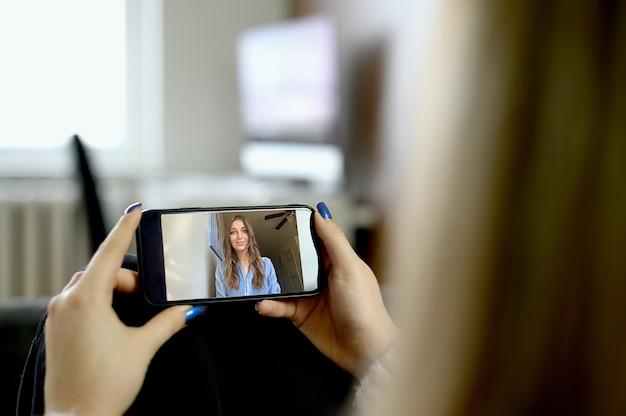 Junge frau, die smartphone für videoanruf verwendet. hochwertiges foto