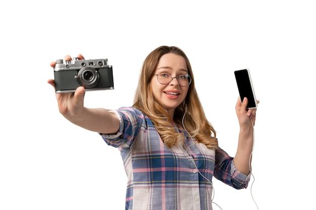 Junge frau, die smartphone, geräte, geräte isoliert auf weißer studiowand verwendet