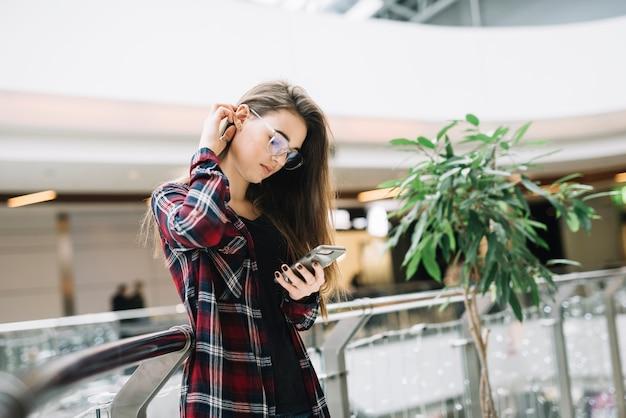 Junge frau, die smartphone im einkaufszentrum verwendet