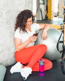 Junge frau, die smartphone nach training in der turnhalle verwendet
