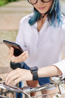 Junge frau, die smartphone und smartwatch synchronisiert, bevor sie fahrrad in der stadt fährt