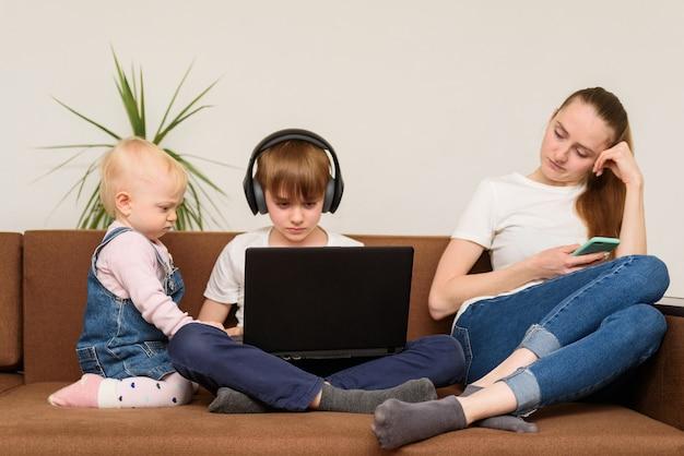 Junge frau, die smartphone verwendet, während kinder im laptop zuschauen.