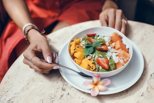 Junge frau, die smoothie im café, glückliches porträt im freien isst