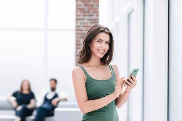 Junge frau, die sms auf ihrem smartphone liest