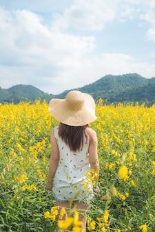 Junge frau, die sommer auf dem gelben gebiet genießt