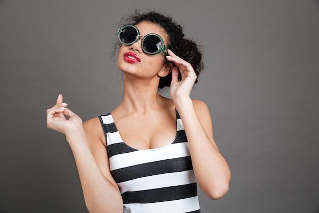 Junge frau, die sonnenbrille und gestreiftes kleid trägt