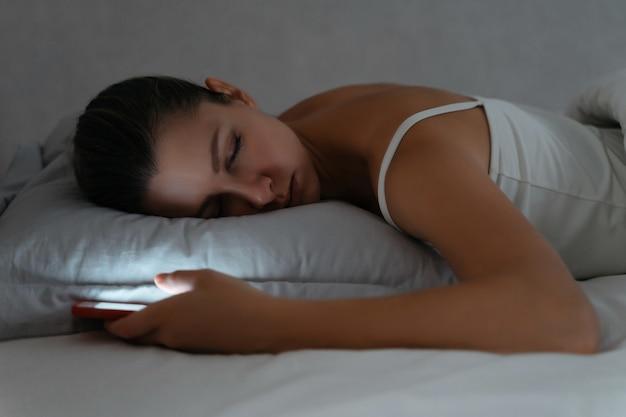 Junge frau, die spät in der nacht auf dem bett mit smartphone in ihrer hand schläft