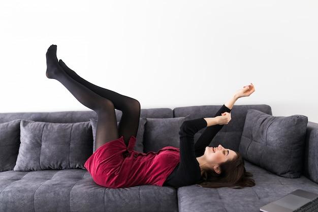 Junge frau, die spaß auf dem sofa beim lügen hat
